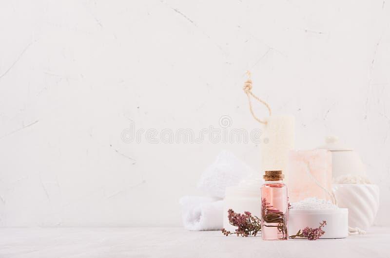 豪华有机身体和护肤温泉化妆用品收藏,桃红色油,花,在白色木背景的自然浴辅助部件 库存图片