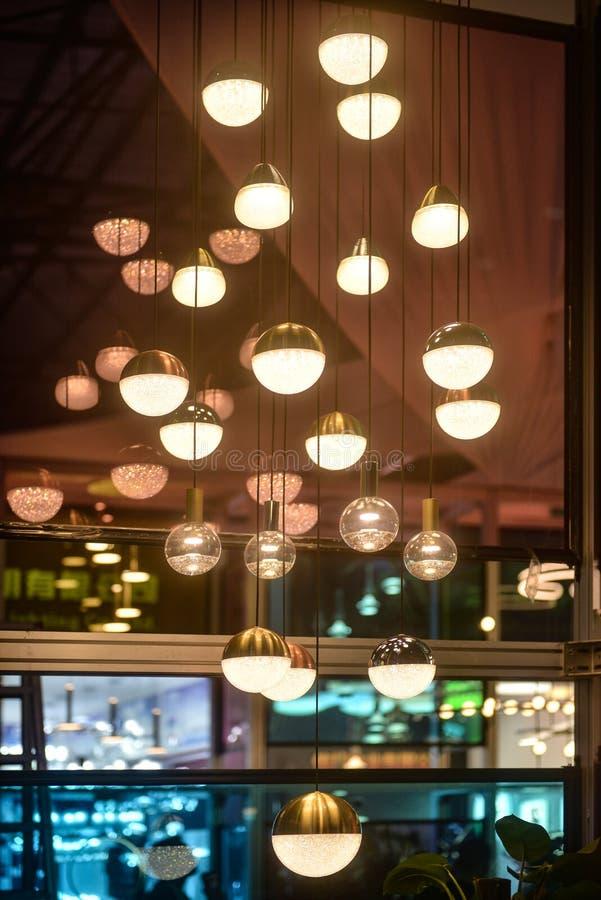 豪华枝形吊灯照明设备在商店窗口里 免版税库存图片
