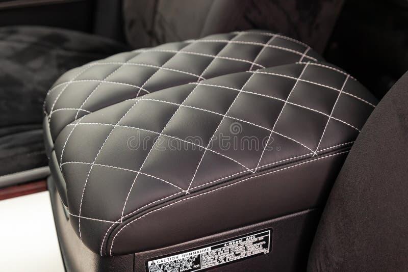 豪华汽车的内部有皮革内部被过分拧紧的缝的以白色螺纹的形式金刚石在中央扶手的 免版税库存照片