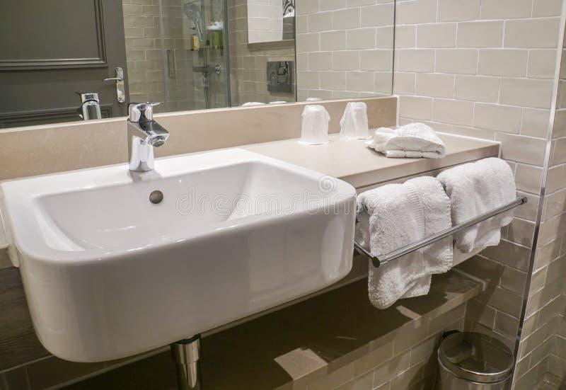 豪华洗涤陶瓷水池和毛巾在卫生间旅馆里 免版税库存图片