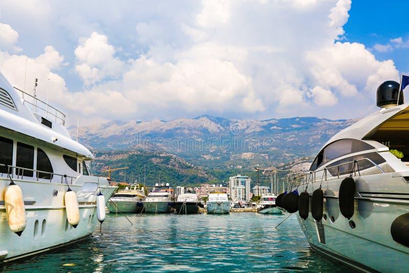 豪华游艇和帆船停泊了在码头在布德瓦小游艇船坞,黑山 口岸在海 白色汽船和风船 库存图片