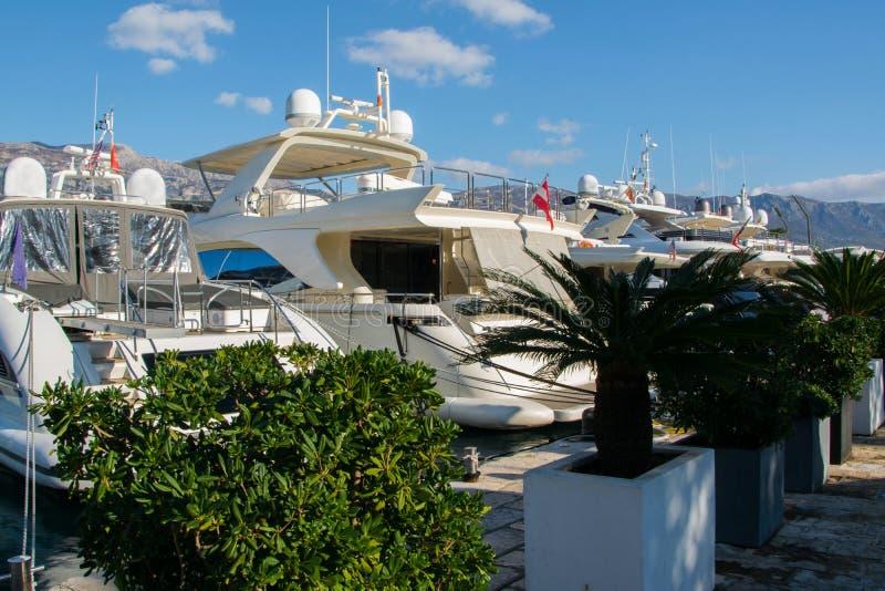 豪华游艇和帆船美丽的景色在地中海城市布德瓦,黑山小游艇船坞港口  风景的山 免版税库存照片