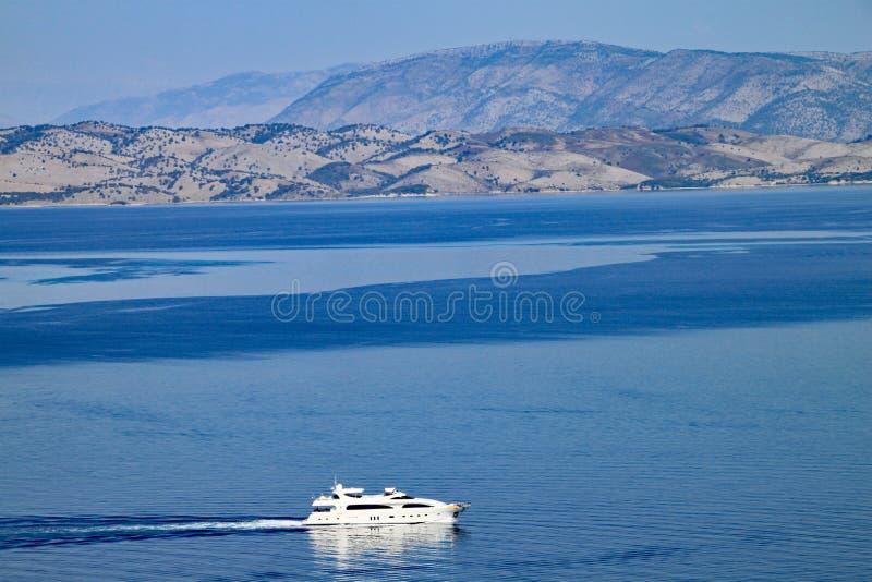 豪华游艇通过科孚岛镇在科孚岛,希腊 阿尔巴尼亚藤茎山在背景中被看见 免版税库存图片