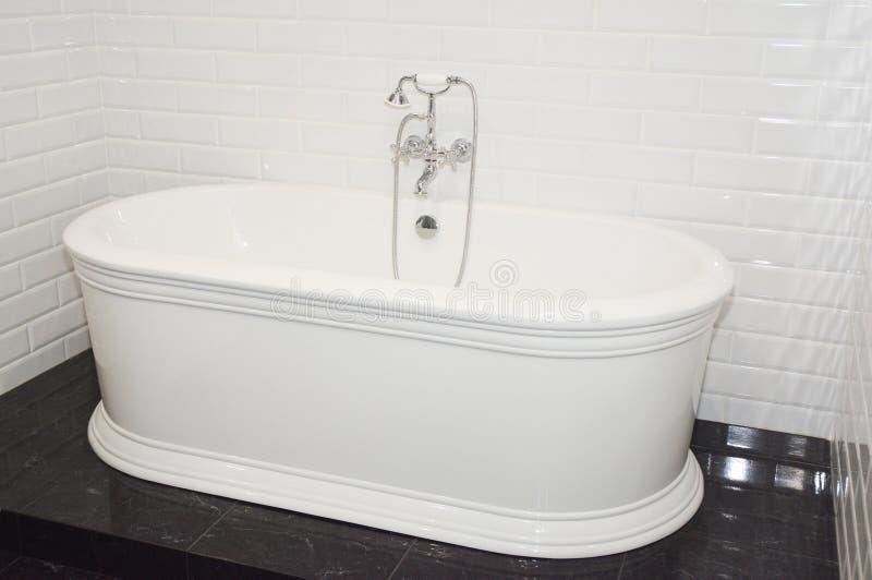 豪华现代浴盆在当代房子卫生间里 免版税库存照片