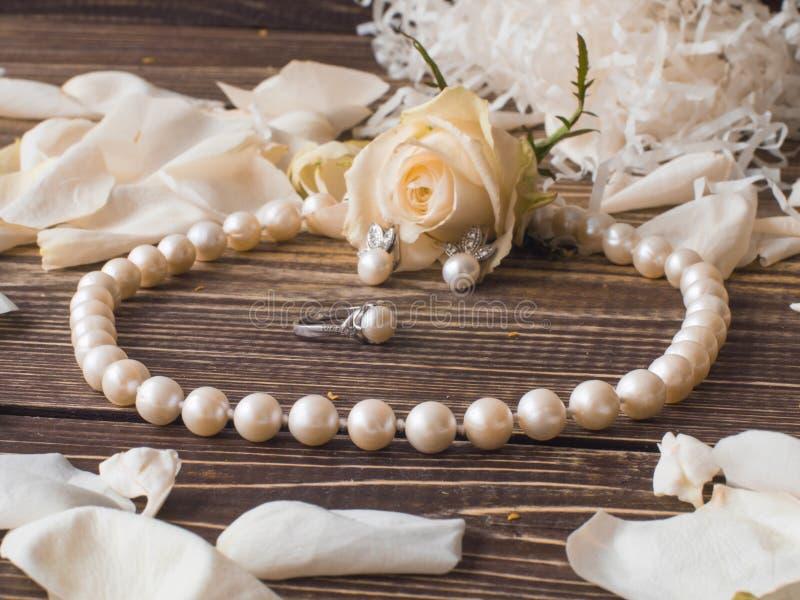 豪华珍珠项链、圆环和耳环有白色玫瑰花瓣的,关闭 免版税库存照片