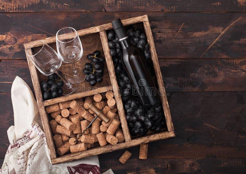 豪华瓶红酒和空的玻璃用黑暗的葡萄与黄柏和拔塞螺旋在葡萄酒木箱里面在黑暗木 免版税库存照片