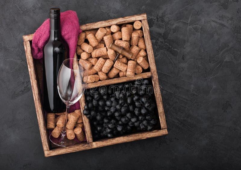 豪华瓶红酒和空的玻璃用黑暗的葡萄与黄柏和拔塞螺旋在葡萄酒木箱里面在黑石头 图库摄影