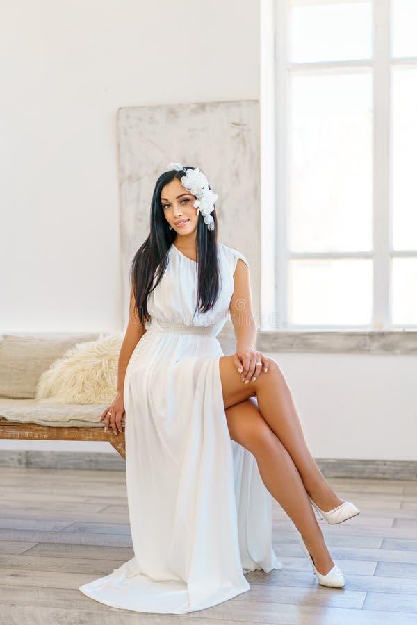 豪华白色礼服的美丽的年轻女人 射击在一个白色演播室 免版税库存照片