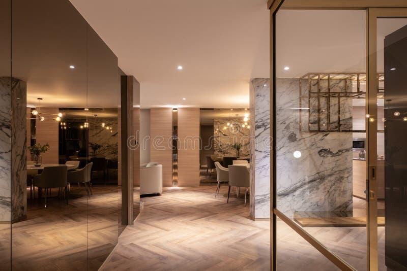 豪华的起居和用餐室装饰有白色大理石和金镜,不带天然木地板 免版税图库摄影