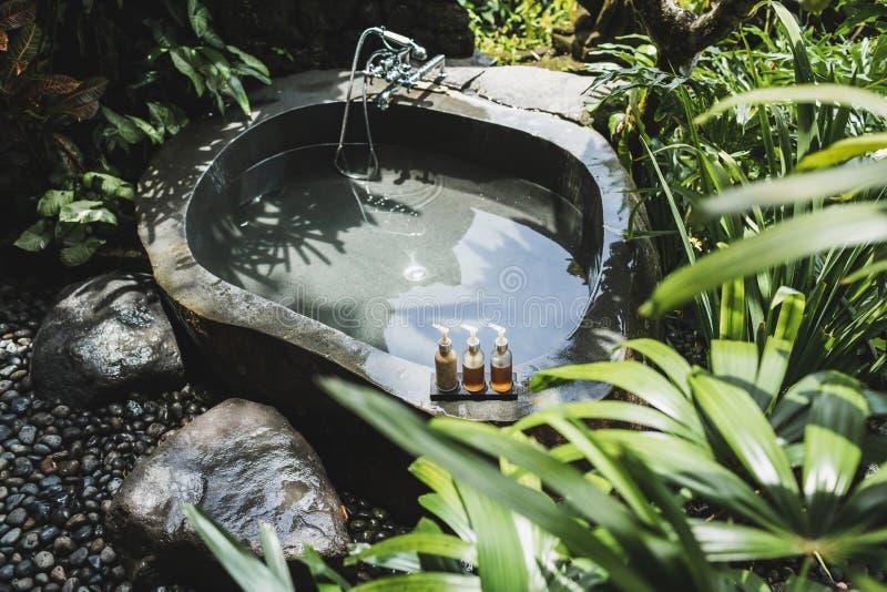 豪华石室外浴在热带绿色密林 图库摄影