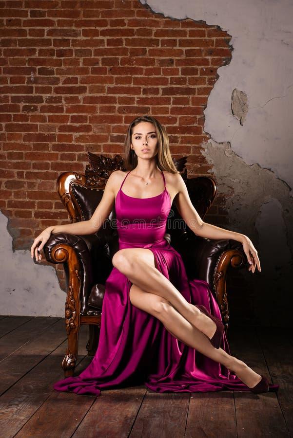 豪华礼服的a壮观的少妇在豪华公寓的一把椅子坐 免版税库存照片
