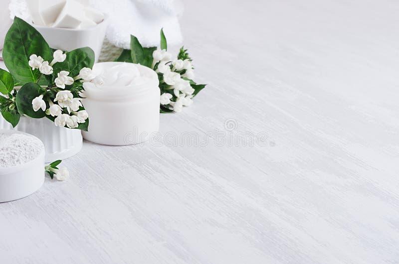 豪华纯净的白色化妆用品被设置身体和护肤的自然产品-奶油,盐,洗刷和在白色木头的小花 库存照片