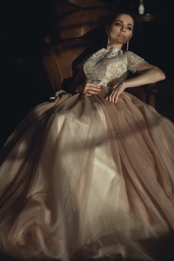豪华设计师礼服的迷人的年轻新娘有在老棕色扶手椅子放松的桃红色遮掩的裙子坐的 免版税库存图片