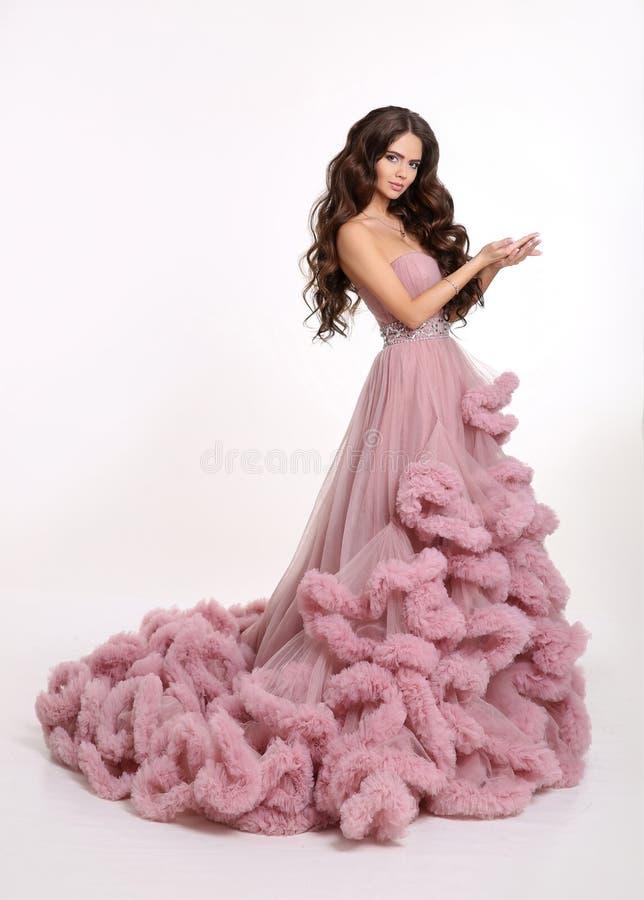 豪华豪华的桃红色礼服的美丽的女孩夫人 美丽的黑色深色的方式头发健康构成 免版税库存照片