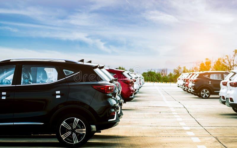 豪华黑色,白色和红色新的suv汽车在具体停车场停放了在有蓝天和云彩的工厂 汽车股票待售 库存图片