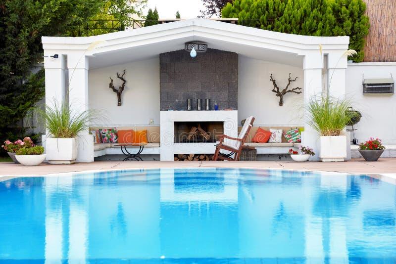 豪华residance的后院露台与游泳场和壁炉的 免版税库存照片