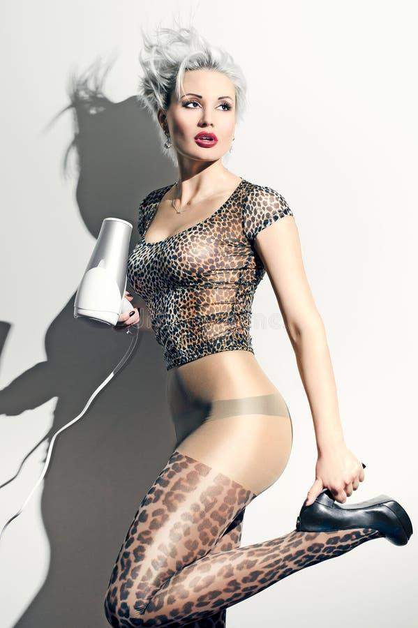 豹子的疯狂的白肤金发的妇女气喘与hairdryer 免版税库存照片