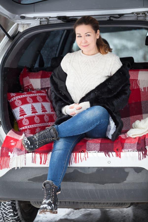 貂皮大衣和羊毛套头衫的妇女在汽车后车箱坐在被打开的后门,冬天森林下 图库摄影