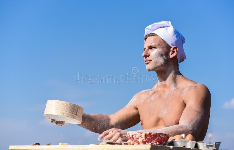 贝克与面粉和筛子,揉的面团一起使用 人肌肉面包师或厨师过滤面粉通过筛子 Pizzaiolo 库存照片