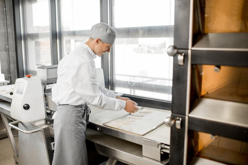 贝克在制造业的辗压面团 免版税图库摄影