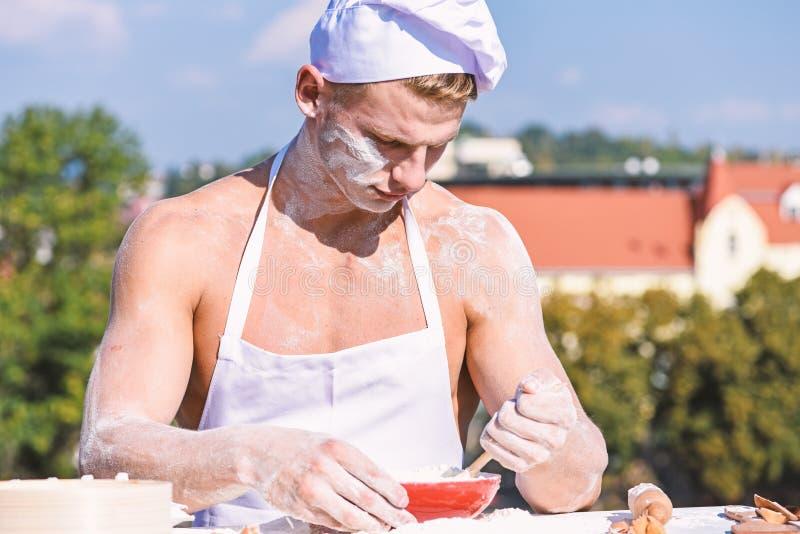 贝克概念 厨师或用面粉盖的厨师有性感的肌肉肩膀的和胸口 繁忙的面孔的人佩带烹调 库存图片