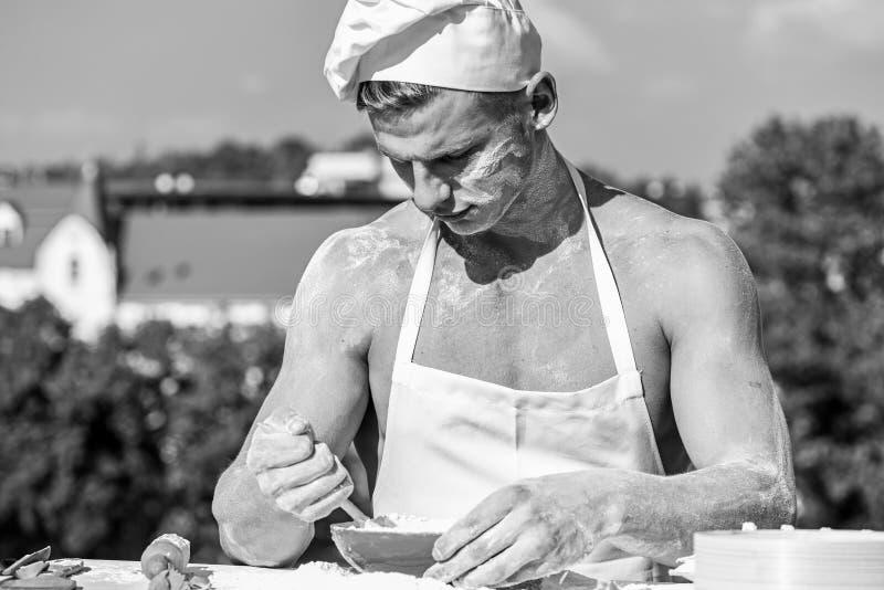 贝克概念 烹调或有肌肉肩膀的用面粉盖的厨师和胸口 繁忙的面孔的人佩带烹调 图库摄影