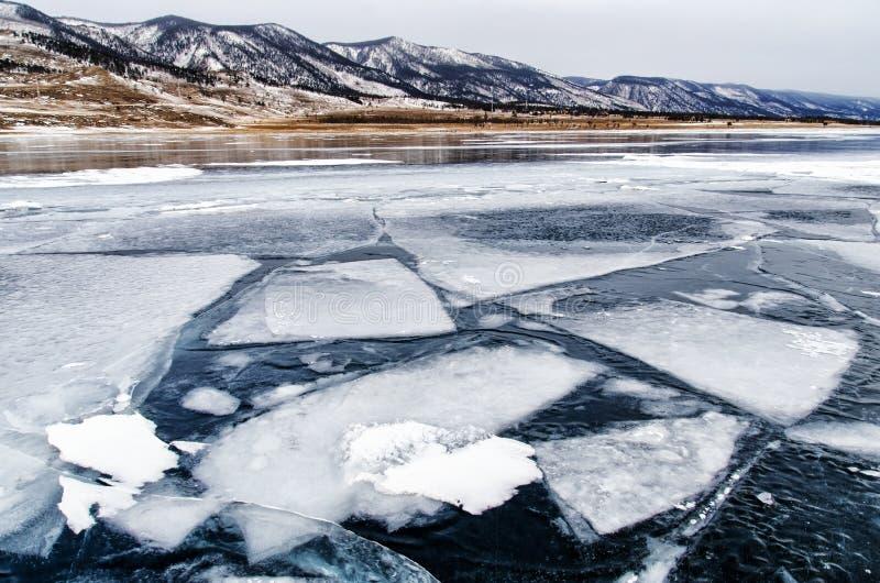 贝加尔湖冻结的湖 在冰表面附近的美丽的山在一冷淡的天 自然本底 库存图片