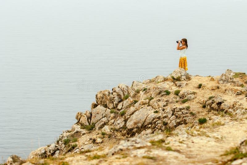 贝加尔湖水面上的一块石头上,站着一个儿童旅行女孩 免版税库存图片