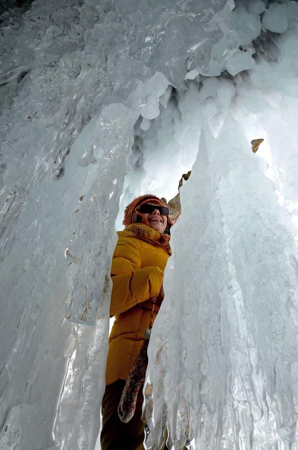 贝加尔湖,俄罗斯- 2018年3月,10:年轻女人在冰洞穴高兴冰钟乳石和stalagnite秀丽  图库摄影