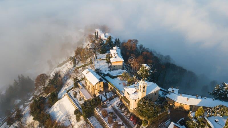贝加莫意大利 雾的一个惊人的风景的寄生虫鸟瞰图从平原上升并且包括圣Vigilio小山  库存图片