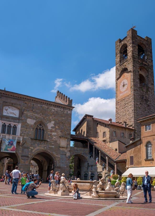 贝加莫,意大利- 2018年5月10日:老正方形在上部镇 与一个时钟的中世纪钟楼在贝加莫 游人 库存图片