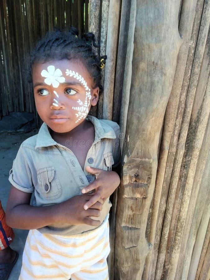 贝岛,马达加斯加- 09/20/2018:有忧郁神色和被绘的面孔神色的非洲孩子在她的小屋外面 库存图片