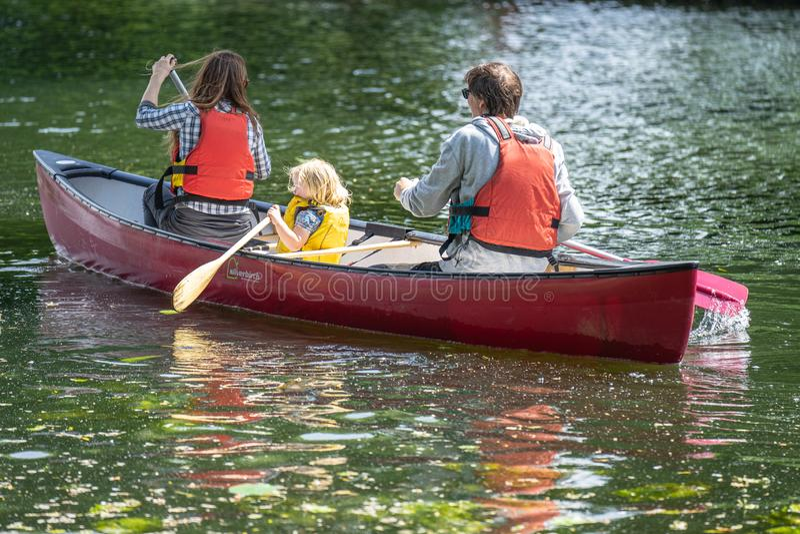 贝得福得,贝德福德郡,英国 2019年6月2日 划皮船的家庭 用浆划在河的皮船的母亲、爸爸和女儿 免版税库存图片