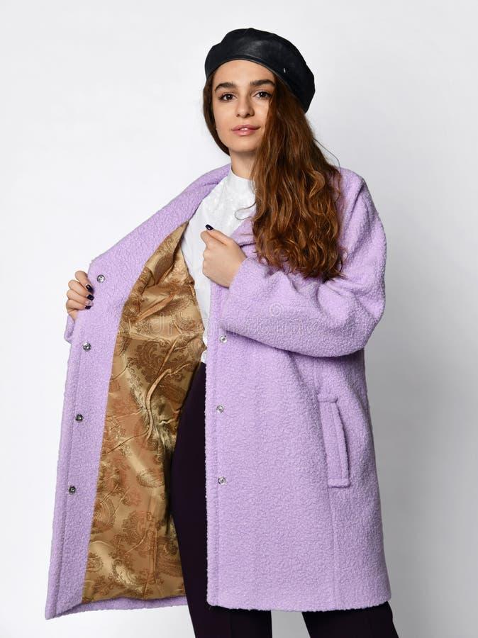 贝雷帽的年轻美女展示排行里面一件新的中等长度时尚偶然桃红色冬天夹克外套 图库摄影