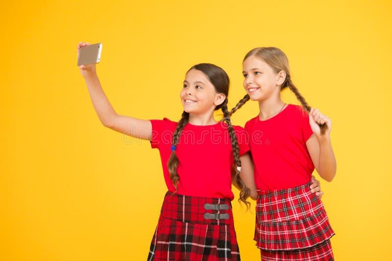 负担是互联网超级明星 女孩采取selfie智能手机 拍完善的照片 女孩要获得乐趣 免版税库存图片
