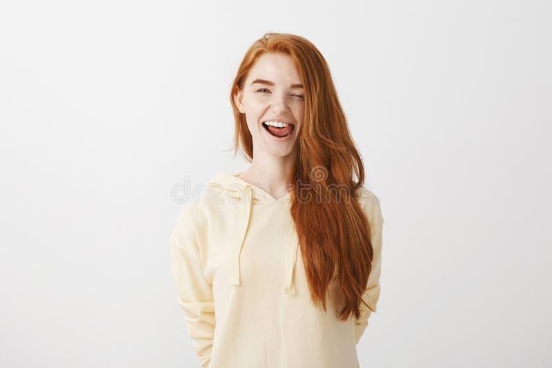负担是反叛和狂放的 悦目正面红头发人女孩画象显示舌头的时髦黄色有冠乌鸦的 免版税图库摄影