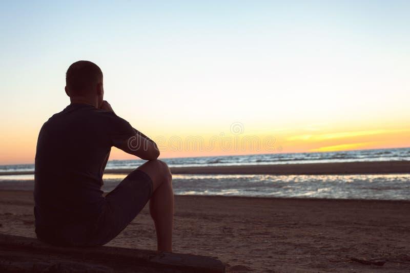 负担由未看见的忧虑 哀伤的孤独的人坐海滩 库存照片