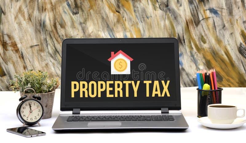 财产税象在膝上型计算机屏幕办公室桌里 免版税库存图片