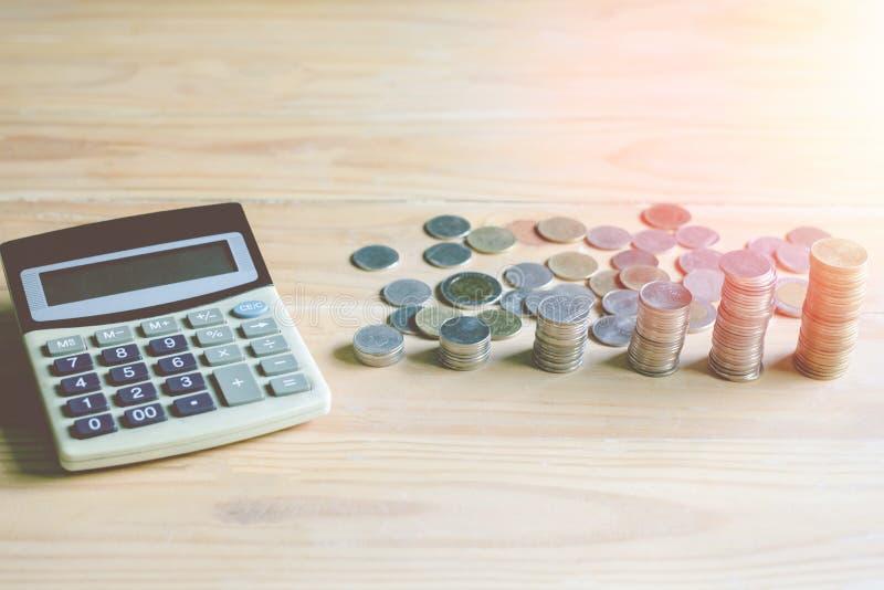 财务会计计算器和硬币在桌上 库存照片