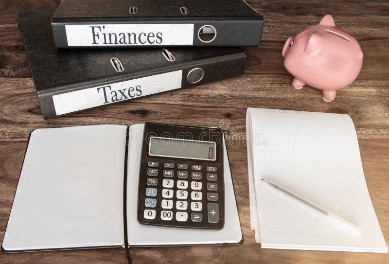 财务和税概念与圆环包扎工具、存钱罐和计算器在木桌上 免版税库存图片