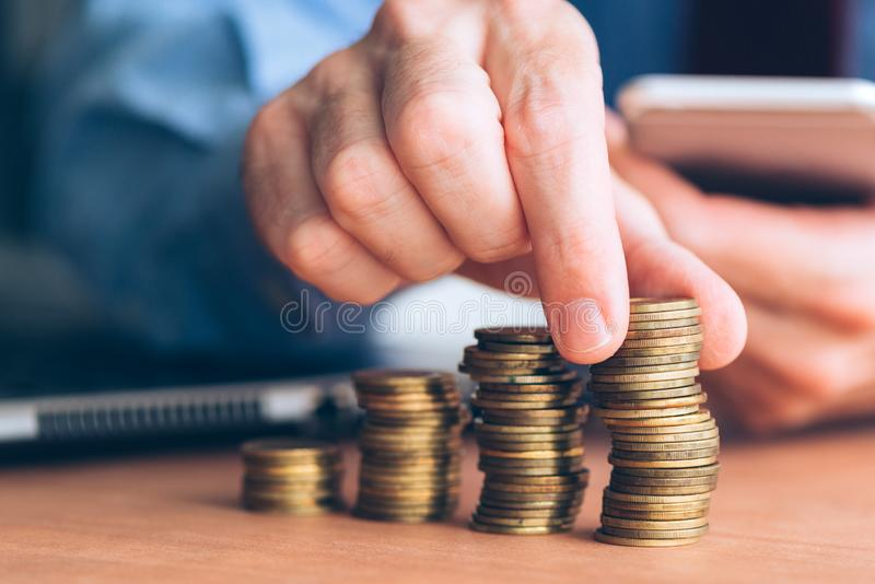 财务和预算,堆积硬币的商人 免版税库存图片