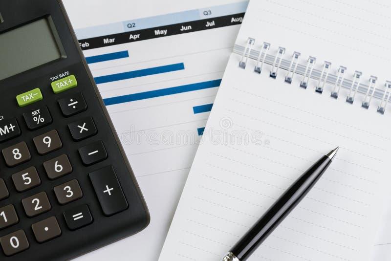 财务或企业季度工作考核概念、计算器、笔与纸笔记关于长条图和图报告文件 免版税库存照片