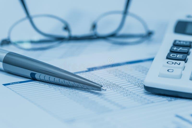 财务,财务分析,认为认为有笔玻璃和计算器的报表在蓝色 关闭股票的概念, 免版税库存照片