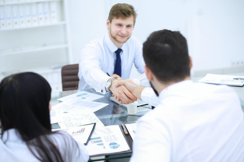 财政伙伴握手在一个业务会议上在办公室 库存照片