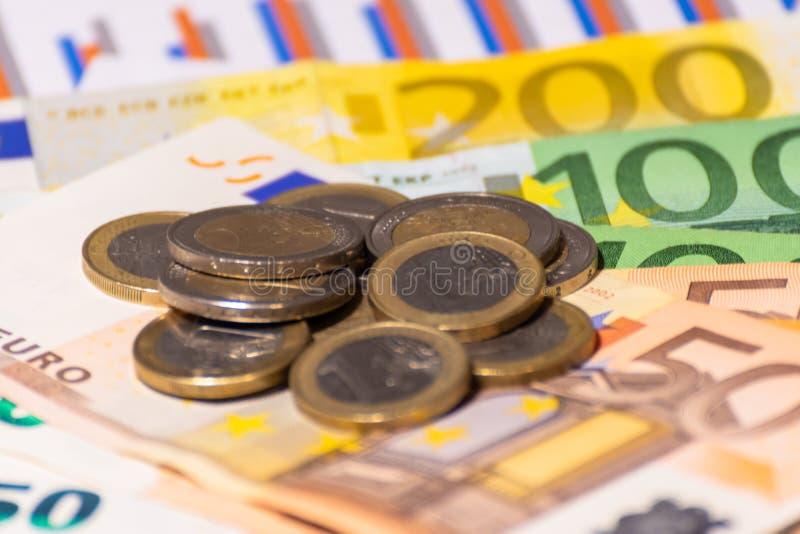 财政报告、硬币和欧元笔记 发单货币 许多欧元钞票和被堆积的硬币 库存照片