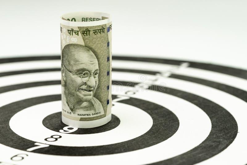 财政目标或目标概念,印度卢比钞票卷被瞄准在黄色掷镖的圆靶的中心 库存照片