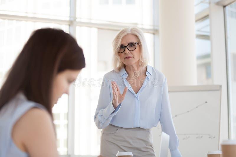 责骂坏工作结果的成熟女性上司实习生紧密  免版税库存图片