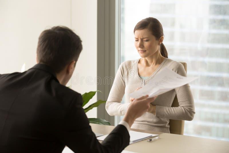 责骂害怕的女性雇员的恼怒的上司 库存照片