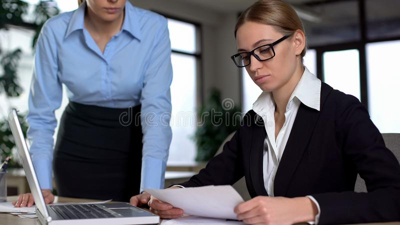 责骂无能实习生的恼怒的上司,不满意对在工作的差错 免版税库存图片