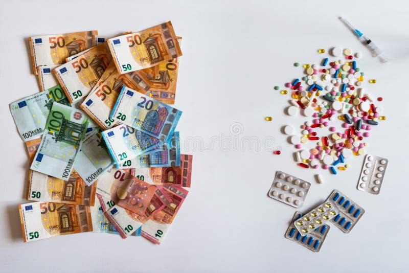 货币和药片 不同的颜色药片在白色背景的 库存照片